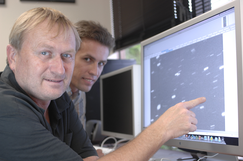 Richard Wainscoat (left) and Marco Micheli study one of the near-Earth asteroids found on January 29. The asteroid is the roundish dot near Wainscoat's finger. IfA photo by Karen Teramura