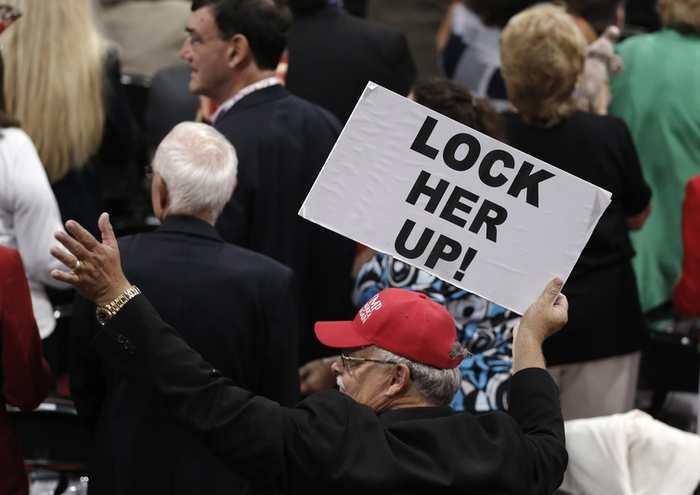 """Un partisan de Donald Trump qui brandit une pancarte pour """"enfermer Hillary Clinton""""."""