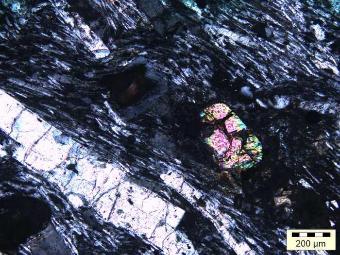 Une roche de type Trachyte en lumière polarisée. Des cristaux de type Alkali feldspar (en blanc) sont alignés sur la gauche par le flux de magma. Et on voit les cristaux de zircon en couleur sur la droite - Crédit : Wits University