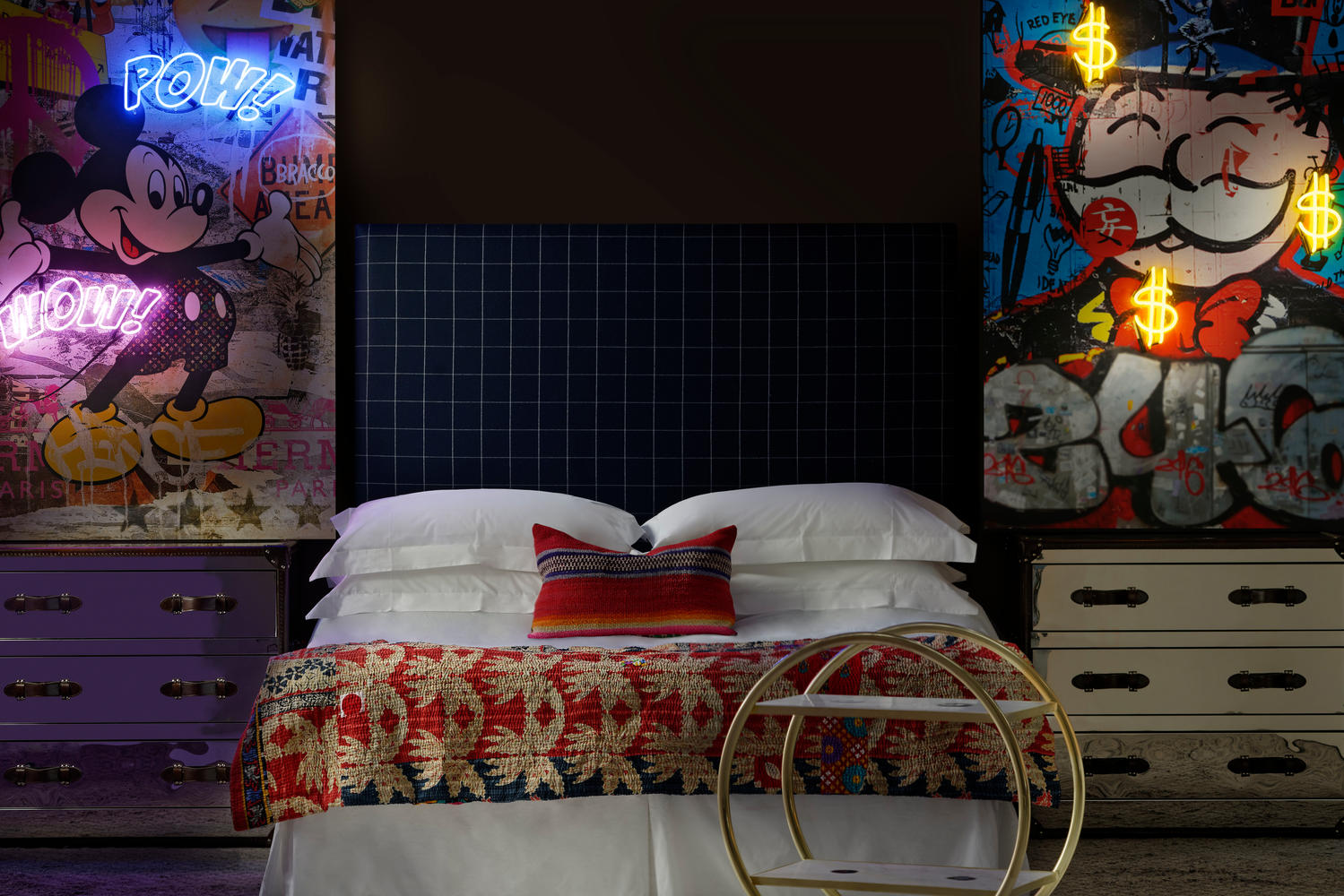 Sage_Custom_Headboard_in_Wales_Navy_with_Howard_steelleather_chest_of_drawers_a_Cici_bar_trolley_and_Micky_Mouse_and_Monopoly_Man_neon_artwork_