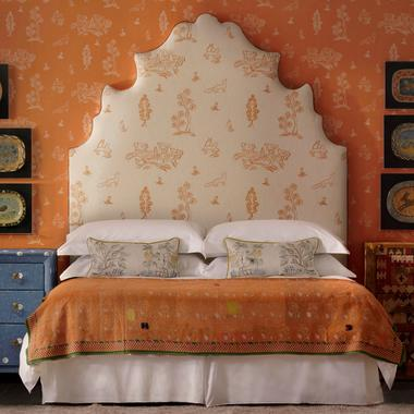 Lucifer_Headboard_upholstered_in_Friendly_Folk_Melon_Orange_Fabric_against_Wychwood_Melon_Orange_Wallpaper_with_chest_of_drawers_in_Over_the_Moon_Denim_Fabric_