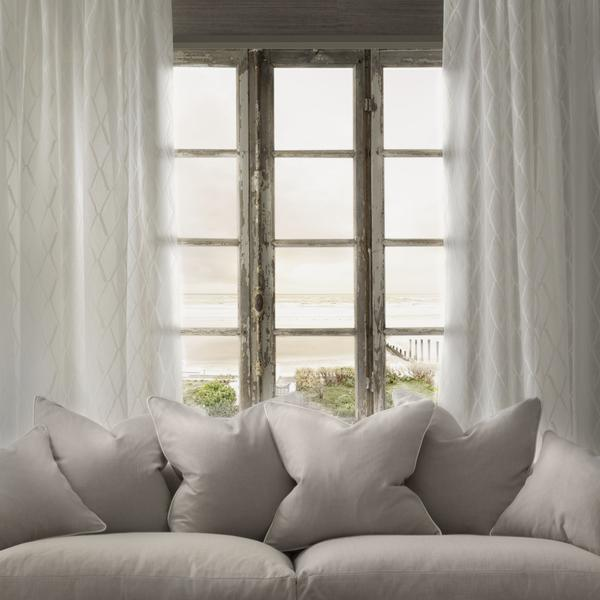 Clementine_Sofa_covered_in_Hammock_Pebble_fabric_with_sheer_curtain_in_Kayak_Ecru