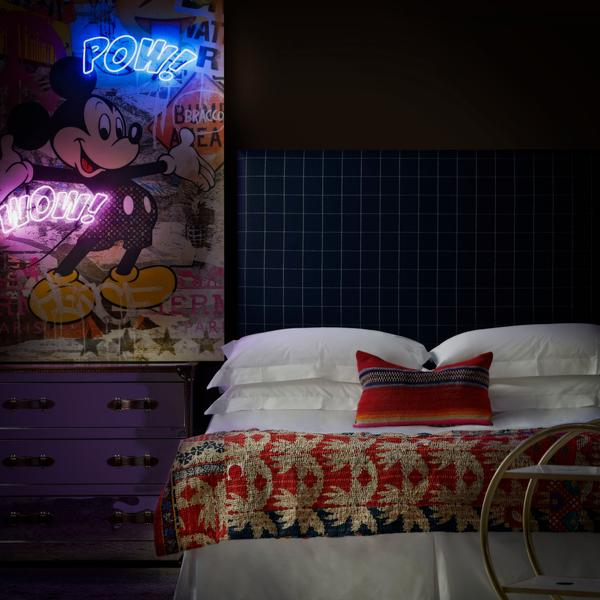 Sage_headboard_in_Wales_Navy_with_Howard_steelleather_chest_of_drawers_a_Cici_bar_trolley_and_Micky_Mouse_Pow_Wow_neon_artwork_