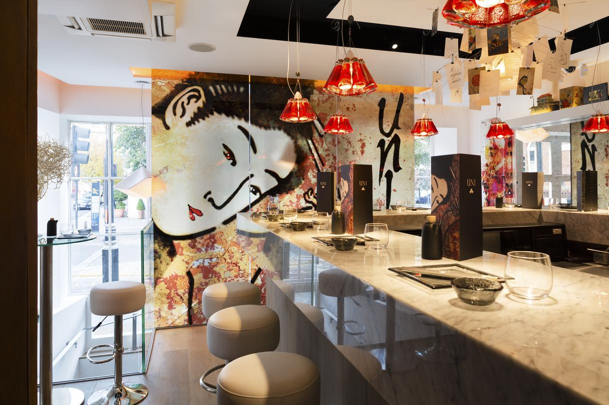 The inspiration for the scheme and furniture of uni restaurant was borne from a commissioned artwork of a japanese geisha in inky black and blossom pinks