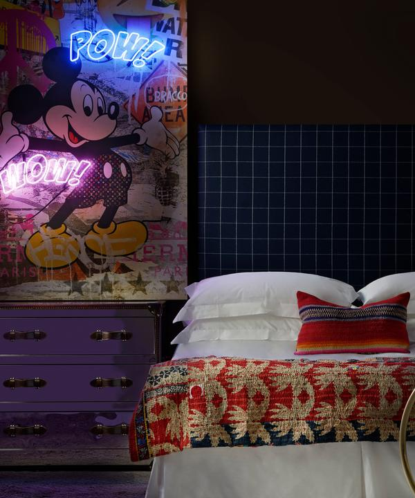 Sage_headboard_in_Wales_Navy_with_Howard_steelleather_chest_of_drawers_a_Cici_bar_trolley_and_Micky_Mouse_and_Monopoly_Man_neon_artwork_