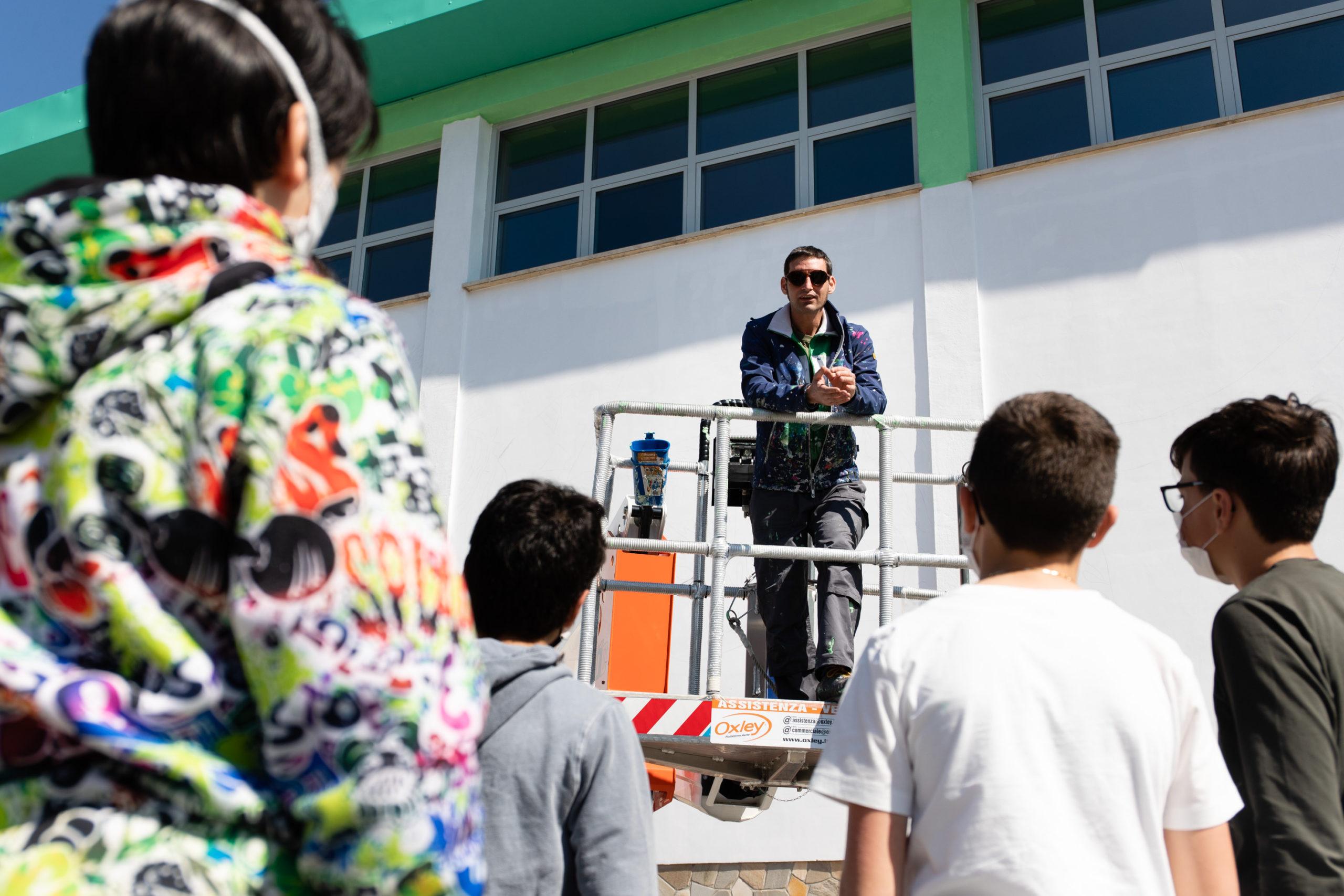 Iena Cruz, street artist milanese al lavoro sulla sulla facciata della scuola media di Madonna dell'Olmo, Cuneo, spiega il suo lavoro agli studenti