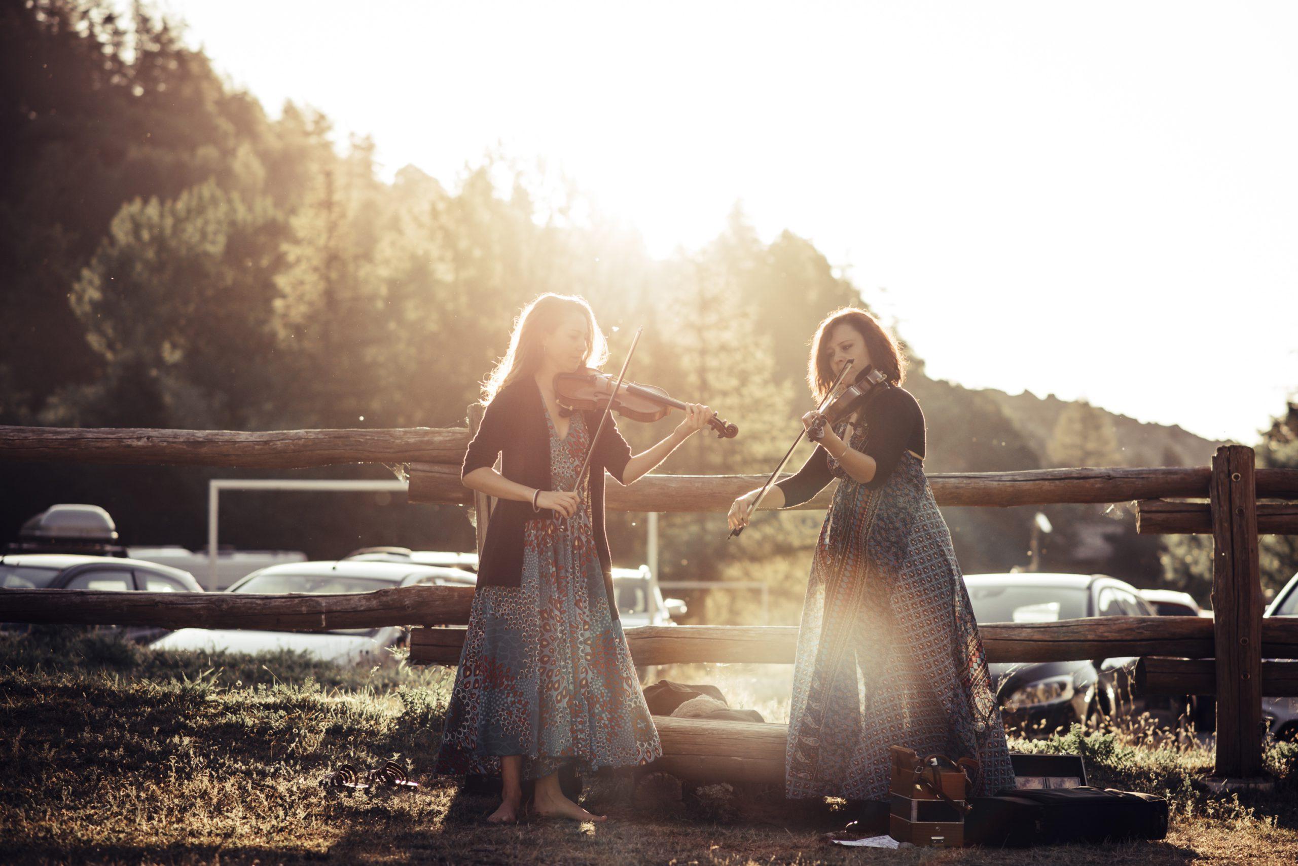 """Una delle """"aubadas"""" del festival Occit'amo: concerti all'alba in rifugio, attendendo il sorgere del sole: due violiniste al sorgere del sole"""
