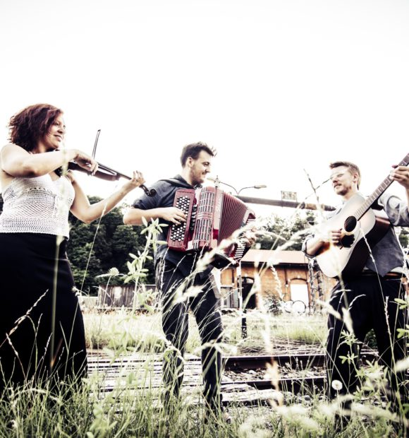Tre musicisti (una donna con violino e due uomini con fisarmonica e chitarra) si esibiscono all'aperto