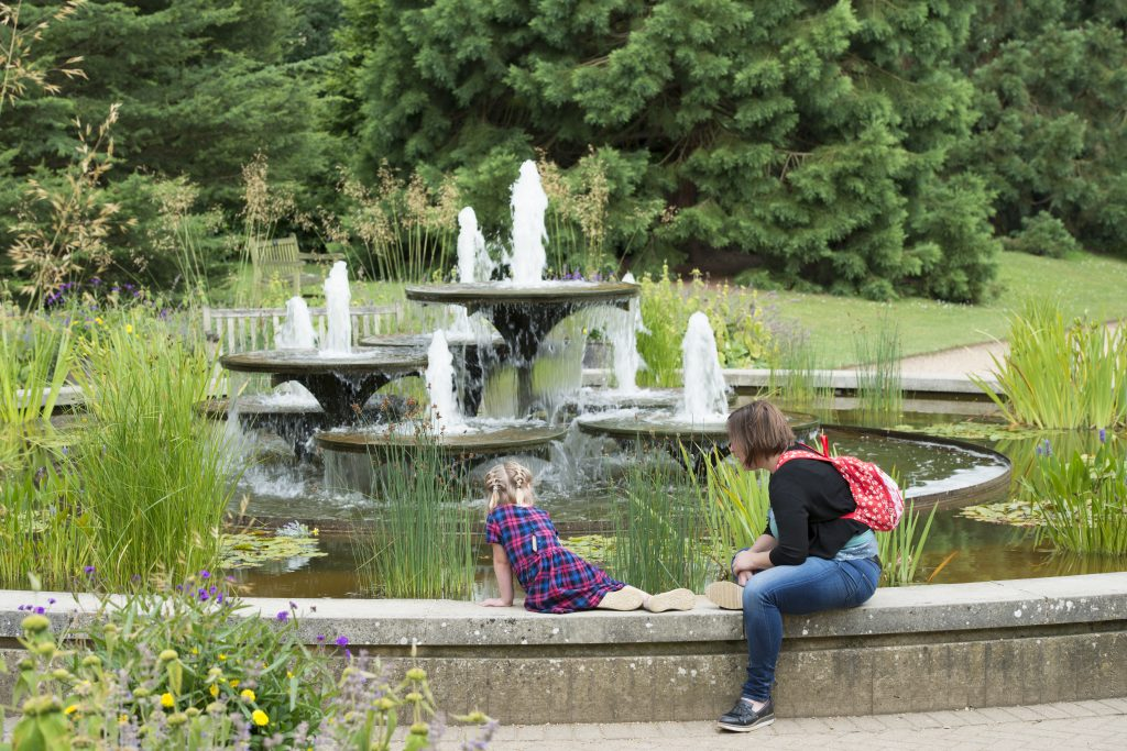 A woman and child sit on the edge of the David Mellor fountain, looking in to the water.