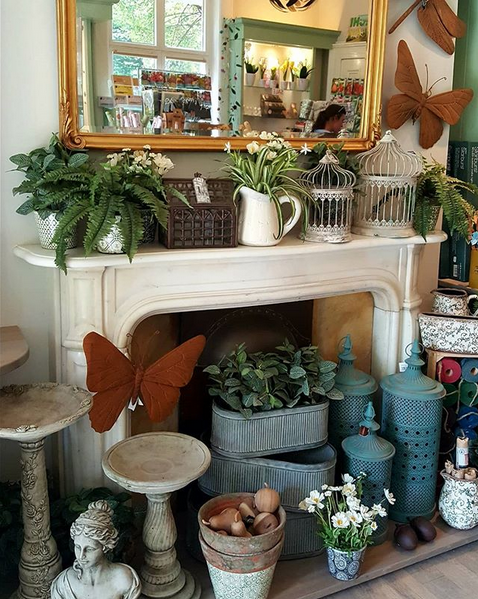A selection of products available at the Garden Shop, such as pots, lanterns, wall decorations and bird baths.