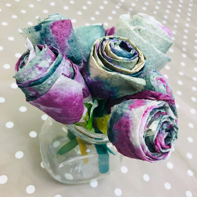 Bouquet of paper flowers coloured shades of purple, blue and green using pigments from blueberries.