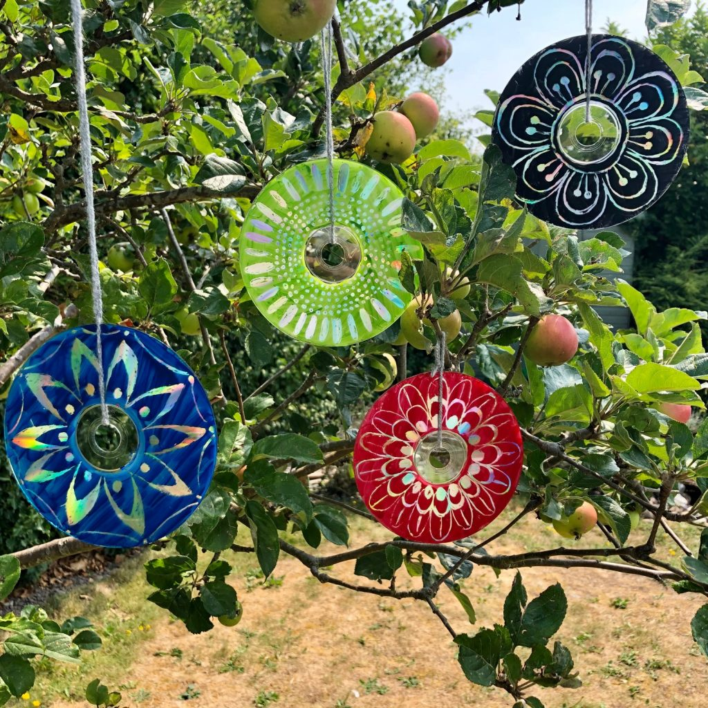 Image of CDs hanging from trees painted like flowers