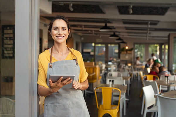 Business owner using free CRM on a tablet in her shop