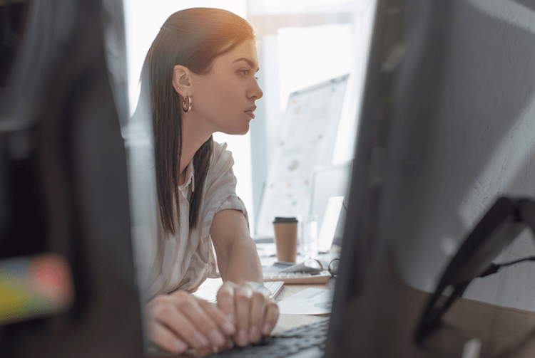 Woman at desk using time and attendance software