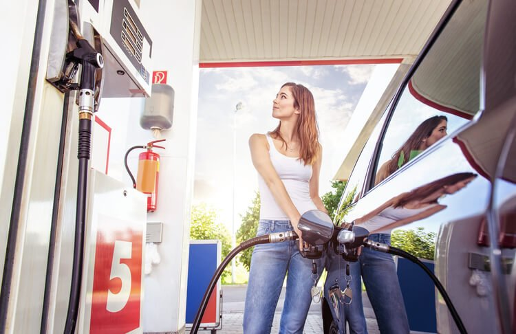 Woman filling up her car at a petrol station