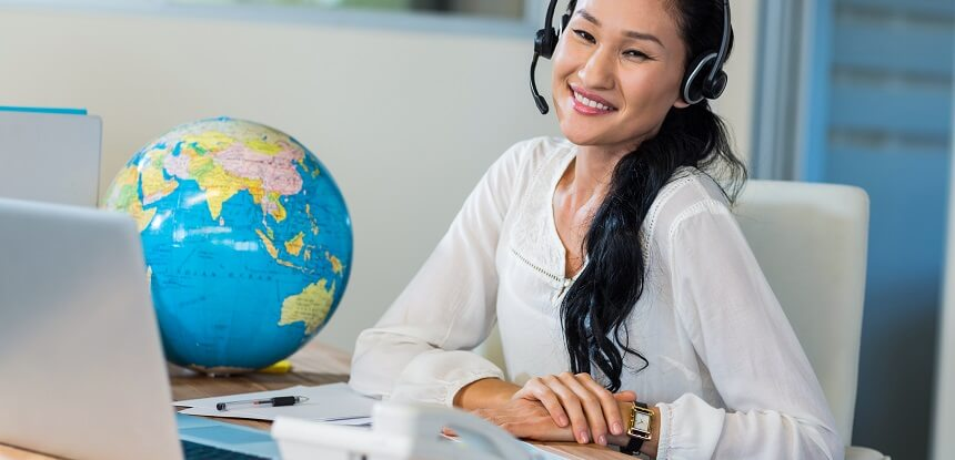 Travel agent smiling at her desk