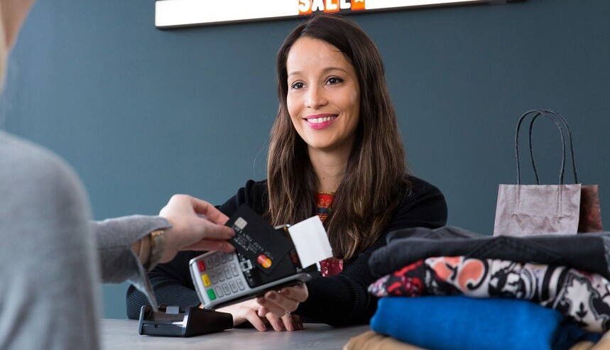 Customer paying for clothes with a card reader