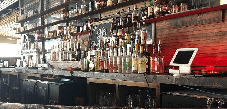 Multiple alcoholic bottles displayed behind a bar