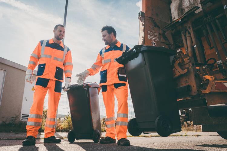 Rubbish men in fluorescent orange collecting waste bins