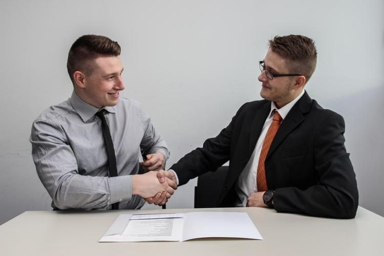 Senior employee and new employee shaking hands