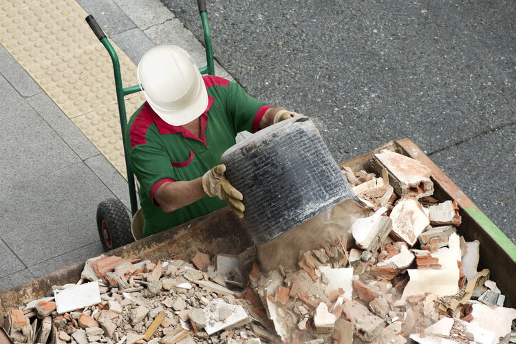 Man in a hard hat disposing waste into skip