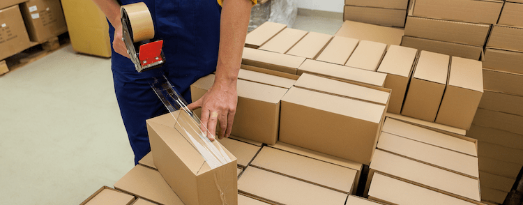 Fulfilment centre employee taping small cardboard boxes shut