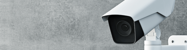 White security camera mounted on grey wall narrow