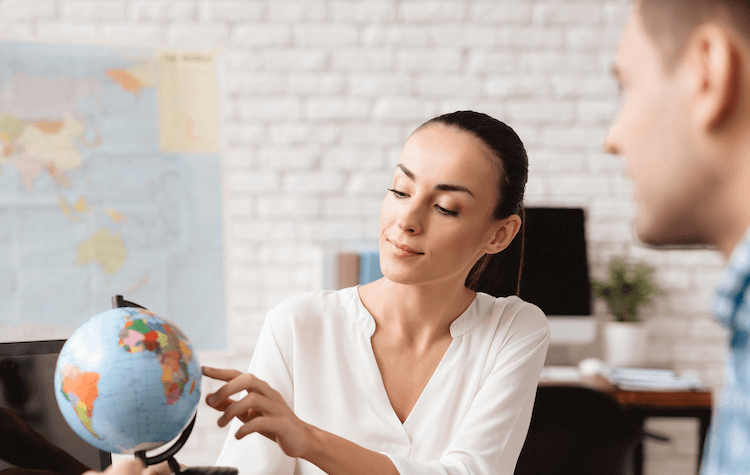 Female travel agent pointing at location on globe with customer