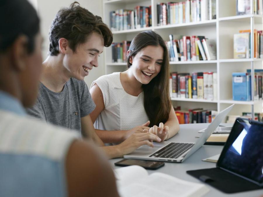 tre smilende studenter foran pc-skjerm