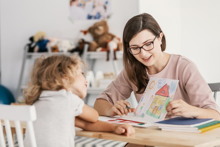 en voksen som peker på et bilde sammen med et barn