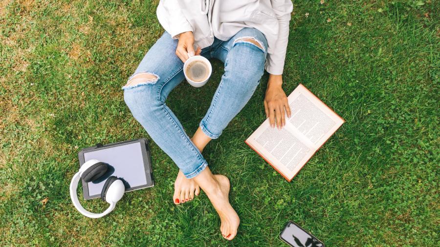 jente med bok ved siden av seg på gresset