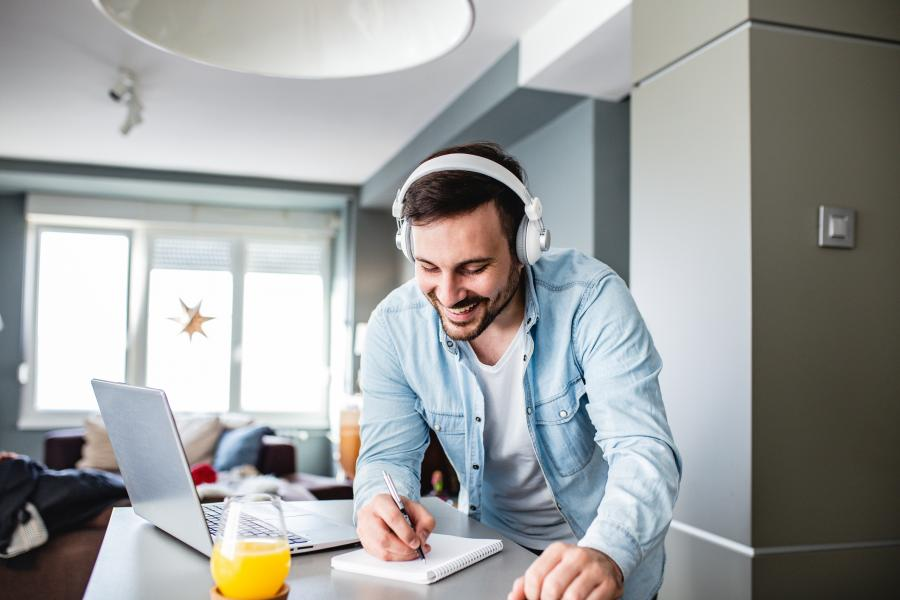 mann som smiler over et bord med øretelefoner