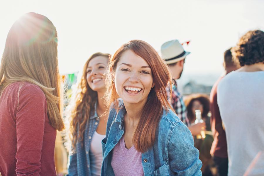 Smilende jente foran utendørs samling av mennesker