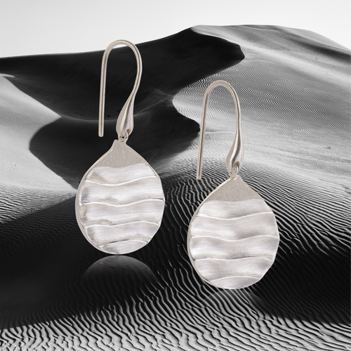 biiju award-nominated silver Careless Rhythm Dune earrings with frosted peaks, shown against a night time sand dune backdrop