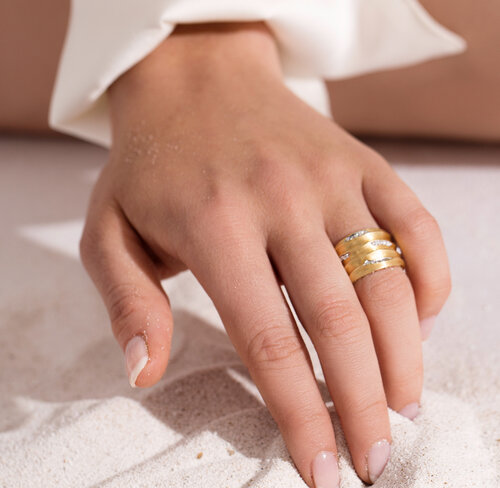 UK Jewellery Awards 2020 finalist biiju's gold Dune ring with diamond-frosted peaks, shown on a hand doodling in sand