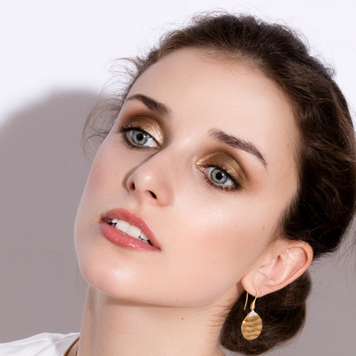 Close up of brunette model Sophie Matthews wearing biiju wavy 18ct gold Dune earrings with sparkling white diamond peaks