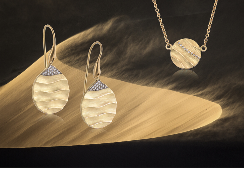 Biiju Dune earrings & necklace shown against the dramatic curves of an African dune, wind whipping the sand up over the ridge