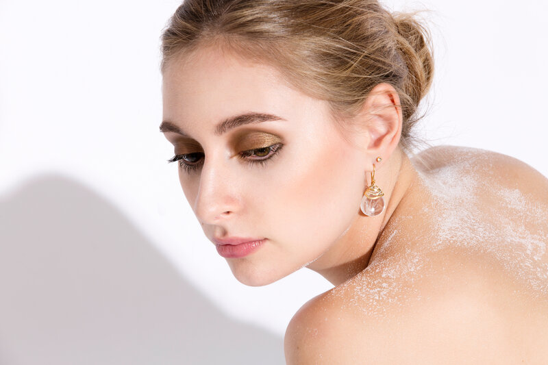 Blonde model Amy Boyen, bare shoulders dusted with white sand, wears the Careless Rhythm collection rock crystal earring