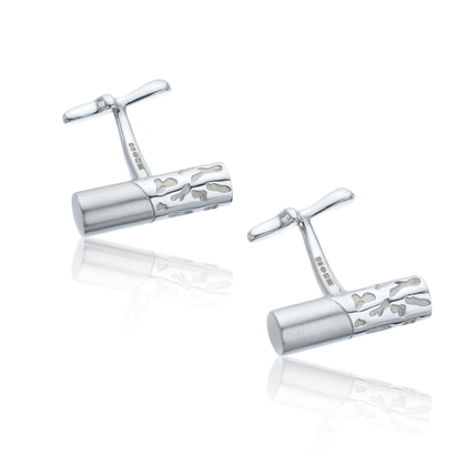 A pair of silver cufflinks with a satin finish, etched camouflage markings & bespoke organically–shaped backs
