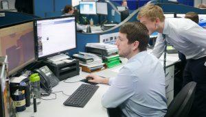 Apprentice overlooks design engineer screen