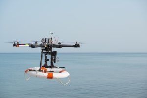 Flight of rescue drone carrying lifebelt
