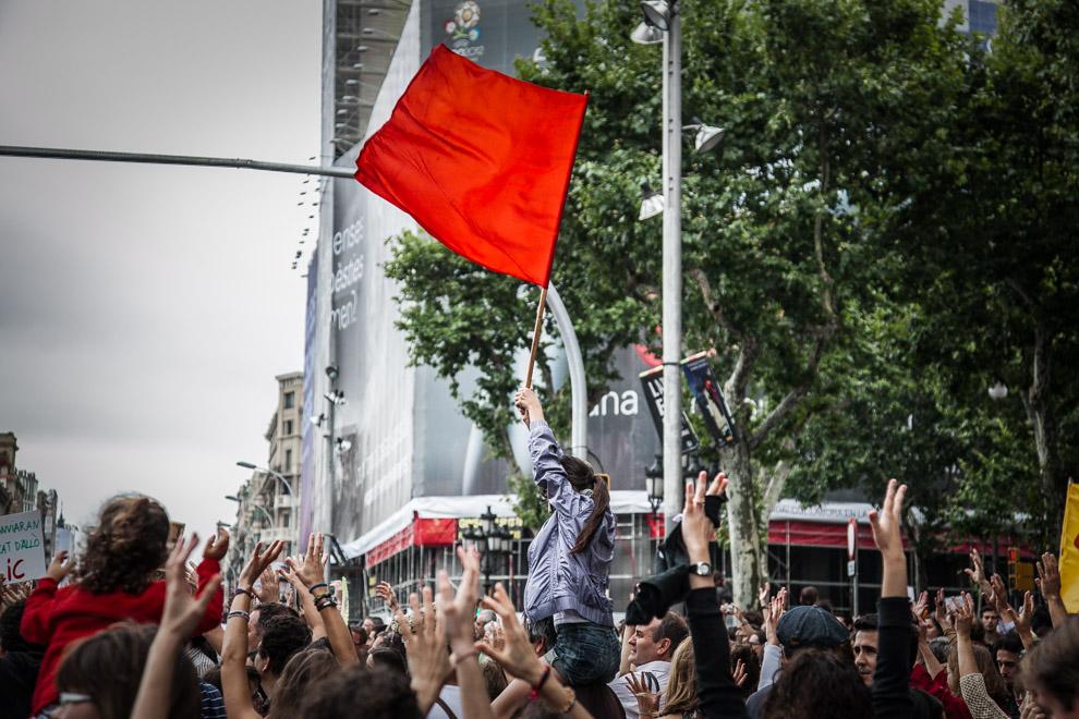 Una noia oneja una bandera roja en una manifestació a Barcelona / JORDI BORRÀS