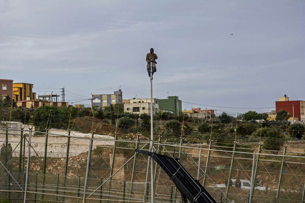 Un immigrant espera a la part més alta d'un fanal a la tanca de Melilla. Es va passar cinc hores fins que l'esgotament el va fer caure a terra / SERGI CÀMARA