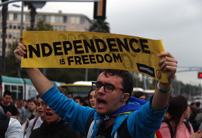 """Primer pla d'un estudiant amb el cartell """"Independence is freedom"""", a la Diagonal de Barcelona."""