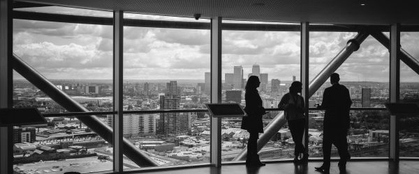 Group of three standing at window looking out onto a city landscape