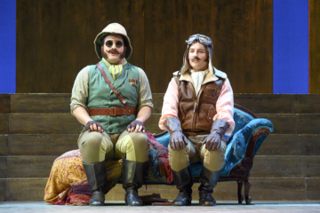 Ferranda and Guglielmo are in disguise and sitting on a chaise longue