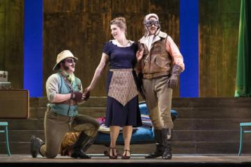Ferrando and Guglielmo sing with Despina. Ferrando is on his knees holding Despina's hand.