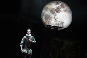 There is a large moon in the background. Aeneas is in the forefront wearing a Tudor outfit and wearing a ruff