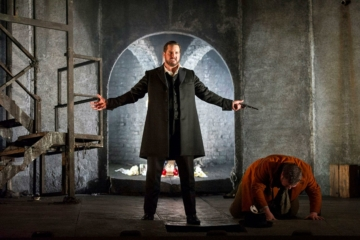 Don Giovanni is standing centre stage, arms wide, with a gun in his left hand. Leporello is on the floor bent over on stage left.