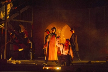 Don Giovanni is on his knees and Il Commendatore is standing above him. Il Commendatore is holding Don Giovanni's hand above a fire pit in the middle of the stage